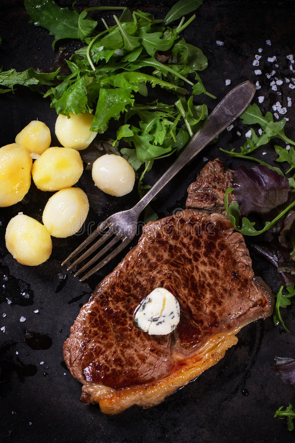 Grilled steak with potatoes. Grilled steak with butter, potatoes and green salad over black metal board royalty free stock photo