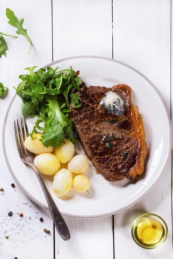 Grilled steak with potatoes. Grilled steak with butter, potatoes and green salad on white ceramic plate over white wooden table. See series royalty free stock photo