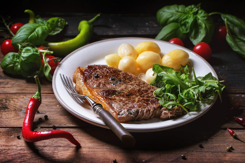 Grilled steak with potatoes. And green salad on white ceramic plate over old wooden table. See series stock photography