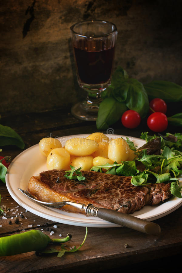 Grilled steak with potatoes. And green salad on white ceramic plate and vintage glass with red wine over old wooden table. See series stock photography