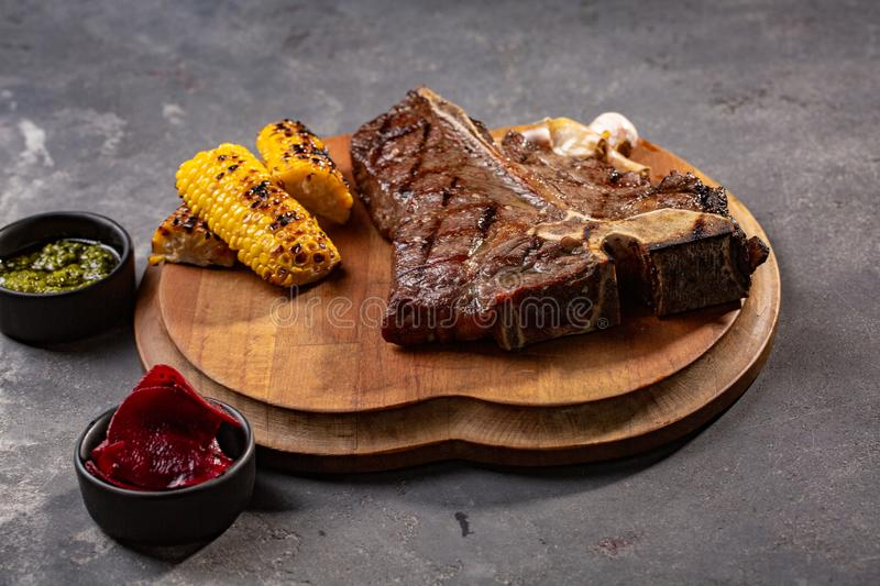 Grilled Steak Ribeye Black Angus with corn on serving board block on wooden background royalty free stock photo