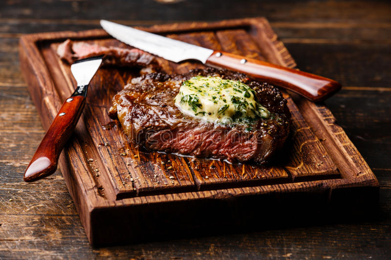 Grilled steak Ribeye with herb butter. Grilled Medium rare steak Ribeye with herb butter on cutting board serving size royalty free stock photography