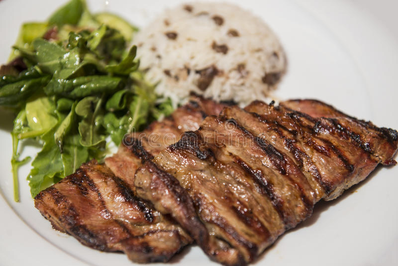 Grilled steak with rice and green leaf salad royalty free stock photos