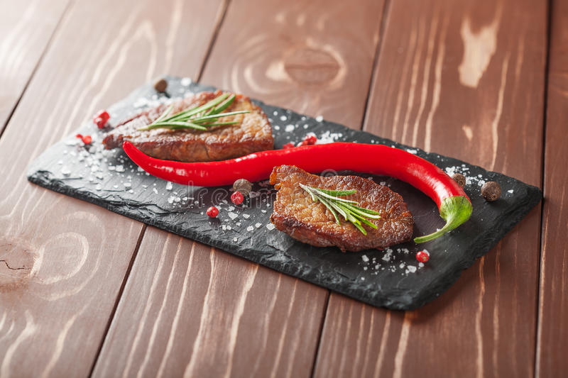 Grilled steak with rosemary and chili peppers on wooden background royalty free stock image