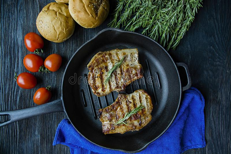 Grilled steak on a round grill pan, garnished with spices for meat, rosemary, greens and vegetables on a dark wooden background royalty free stock photography