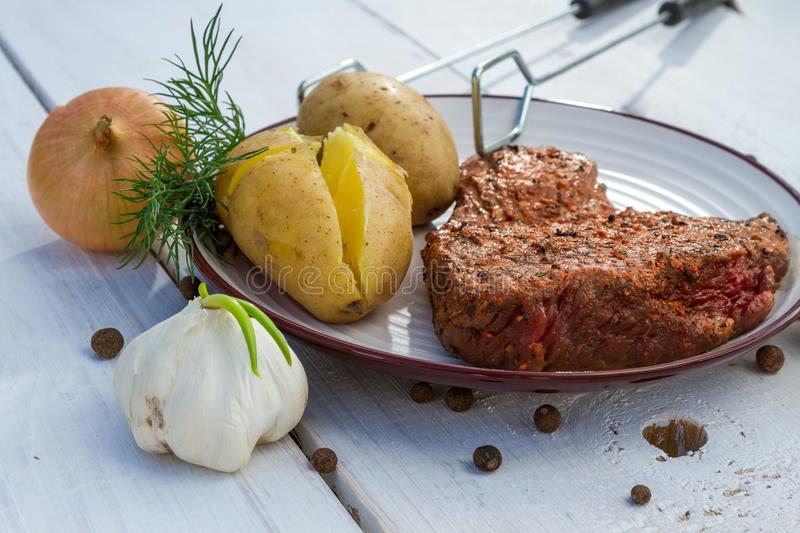 Grilled steak served with potatoes royalty free stock photos