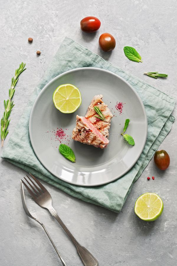 Grilled steak tuna fish with lime on a gray background. Top view, flat lay.  stock photography