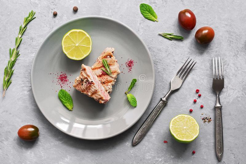Grilled steak tuna with lime on a gray background. Top view, flat lay.  royalty free stock photo