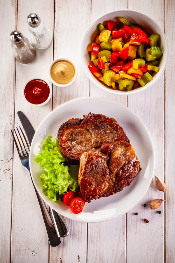 Grilled steak and vegetables on wooden background royalty free stock image