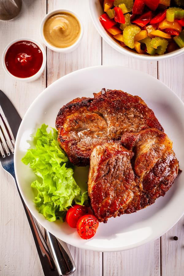 Grilled steak and vegetables on wooden background stock images