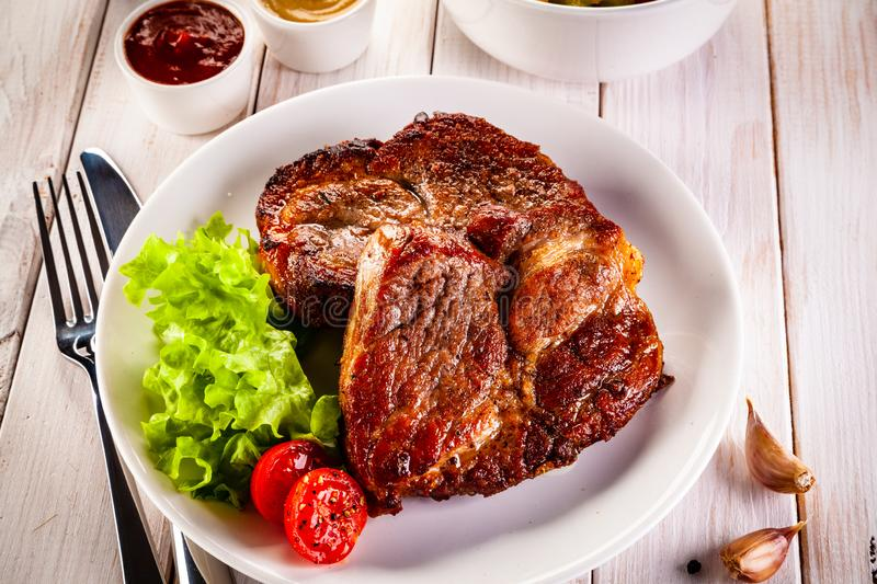 Grilled steak and vegetables on wooden background stock photos