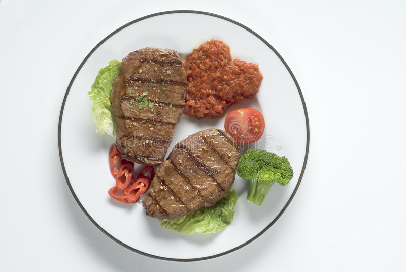 Grilled steaks. Grilled medium well steaks with relish and vegetable garnish stock photos