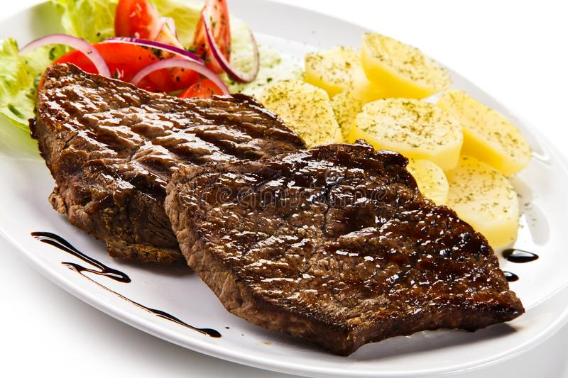 Grilled steaks, boiled potatoes and vegetable salad. On white background royalty free stock photography