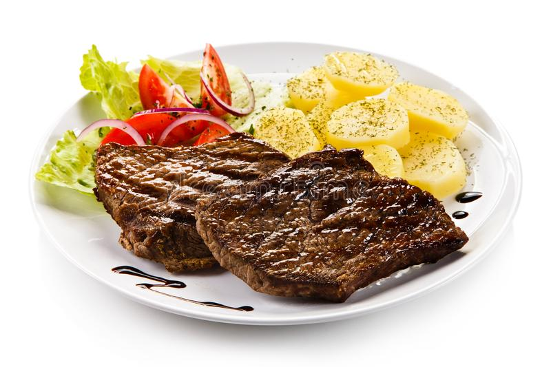 Grilled steaks, boiled potatoes and vegetable salad. On white background royalty free stock photos