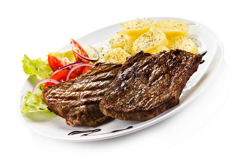 Grilled steaks, boiled potatoes and vegetable salad. On white background royalty free stock images
