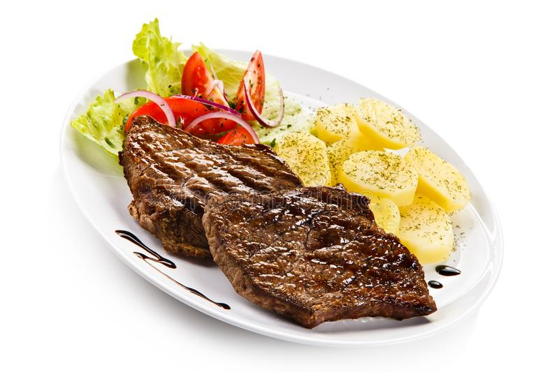 Grilled steaks, boiled potatoes and vegetable salad. On white background royalty free stock photo