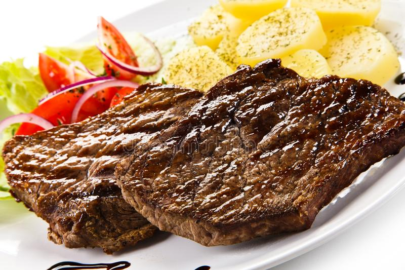 Grilled steaks, boiled potatoes and vegetable salad. On white background stock image