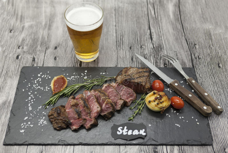 Grilled striploin steak on a stone plate with a glass of beer with a fork and knife. stock photos