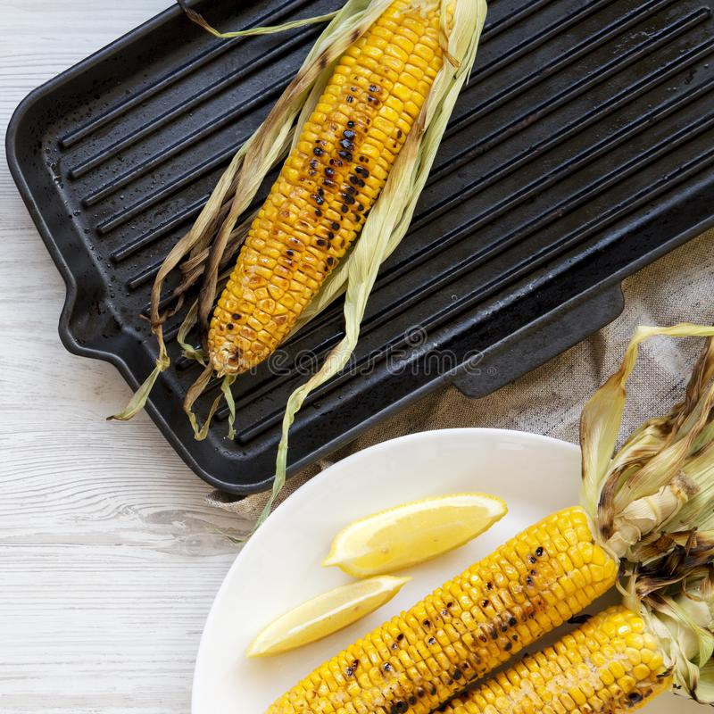 Grilled sweet corn on a white wooden background, top view. Summer vegan snack. Healthy diet. Close-up stock photo