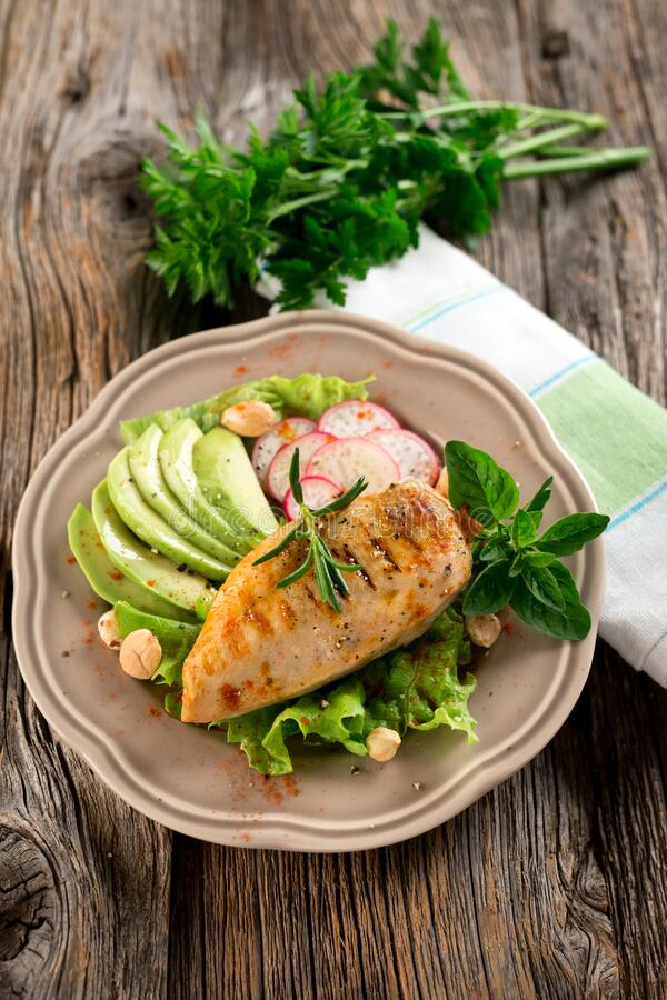 Grilled tasty chicken breast with avocado stock image