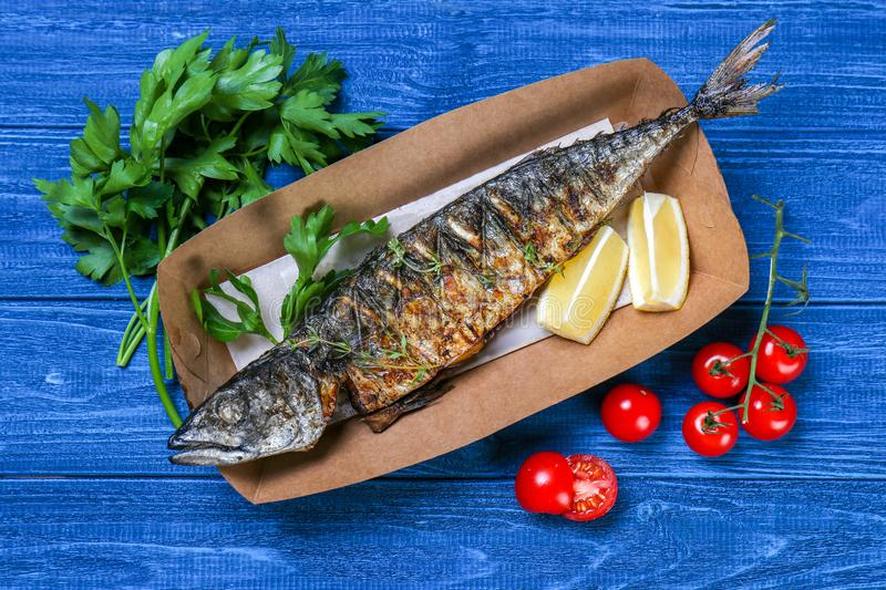 Grilled tasty fish in paper box royalty free stock images
