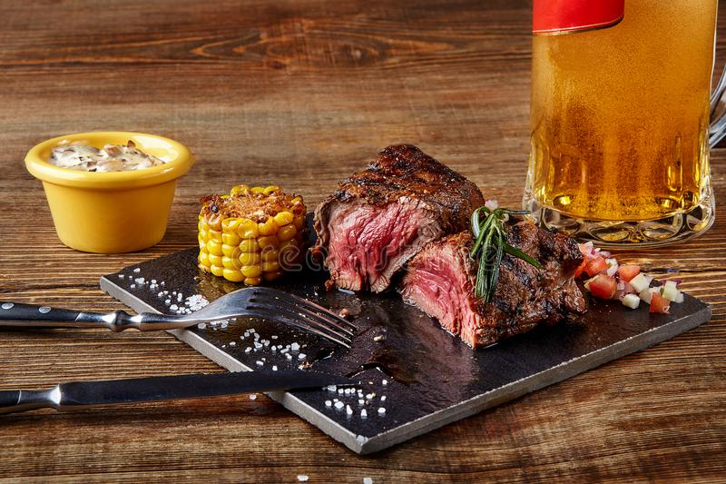 Grilled tenderloin Steak roastbeef and mushrooms sauce on black cutting board and glass of beer on wooden background. Serving a ready meal in a restaurant stock photos