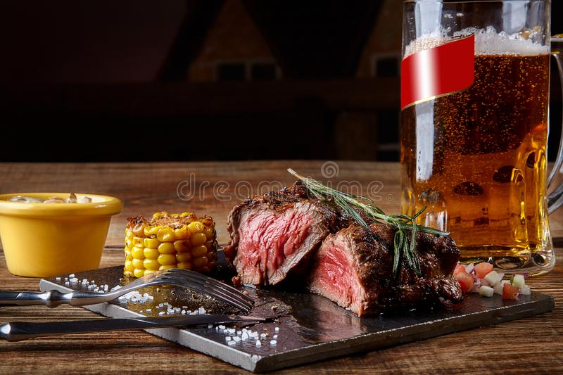 Grilled tenderloin Steak roastbeef and mushrooms sauce on black cutting board and glass of beer on wooden table. Serving a ready meal in a restaurant, cafe royalty free stock image