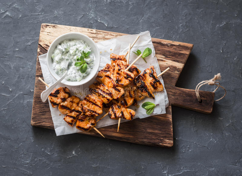 Grilled teriyaki chicken skewers and tzatziki sauce on a wooden board on a dark background, top view. royalty free stock photography