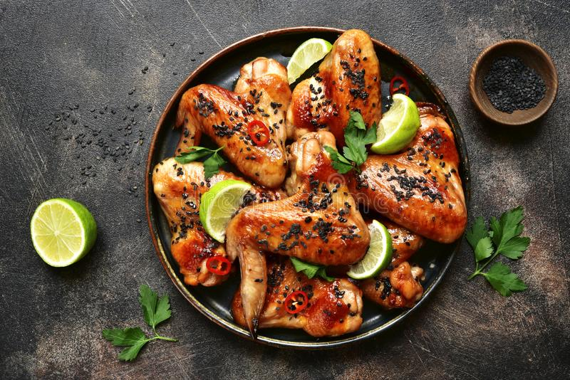 Grilled teriyaki chicken wings with black sesame and lime.Top vi stock photography