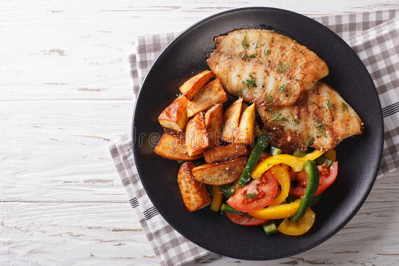 Grilled Tilapia fillet and potato wedges, fresh salad close-up. Grilled Tilapia fillet and potato wedges, fresh salad on a plate close-up. Horizontal view from royalty free stock photography