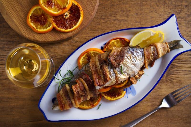 Grilled tocino-envolvió pescados con las naranjas y el romero, servidos con los limones fotografía de archivo