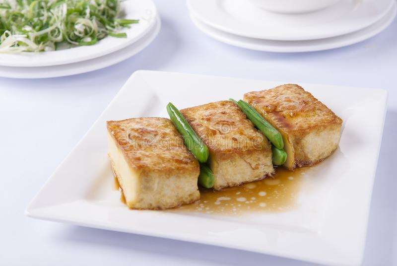 Grilled tofu and french bean. On dish with white background stock photos