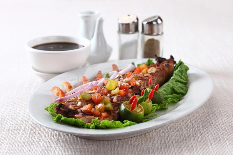 Grilled tuna belly. Grille dtuna belly on white plate with dipping sauce royalty free stock photography