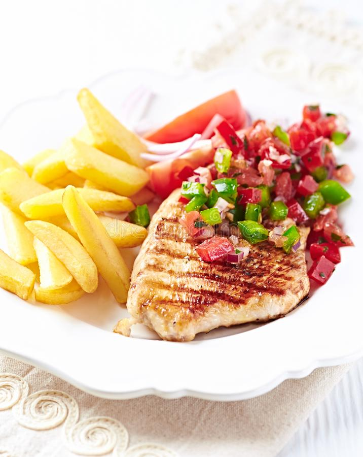 Grilled turkey breast with salsa and french fries stock image