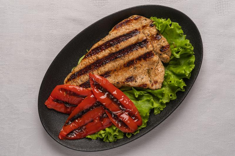 Grilled turkey breast steak with baked peppers and lettuce leaves in a black oval plate on a light linen background. Homemade grilled turkey breast steak with stock photos