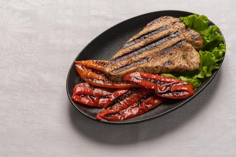 Grilled Turkey breast steak with baked peppers and lettuce leaves in a black plate on a light linen background. Homemade grilled turkey breast steak with baked stock images