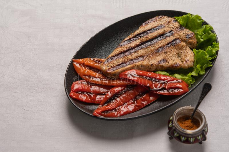 Grilled Turkey breast steak with baked peppers and lettuce leaves in a black plate on a light linen background. Next to. Homemade grilled turkey breast steak royalty free stock photos