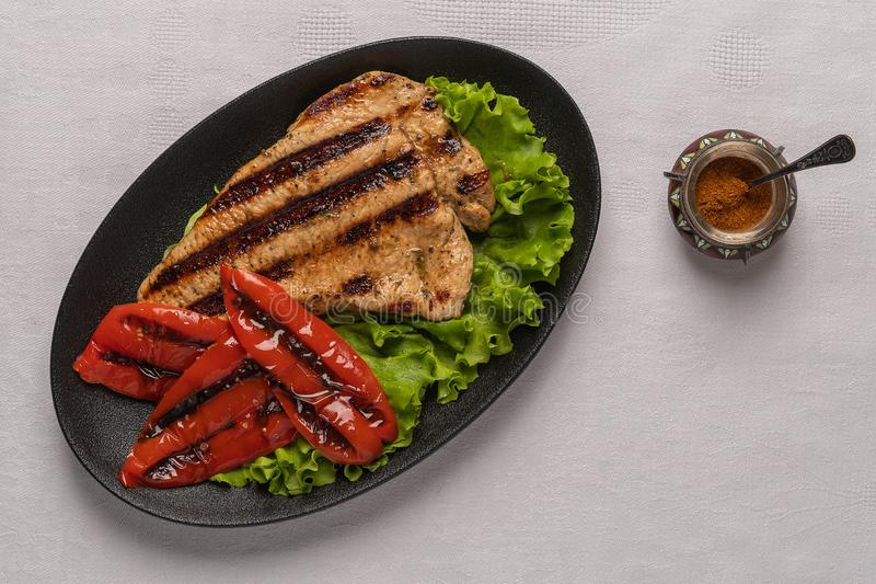 Grilled turkey breast steak with baked peppers and lettuce leaves in a black plate on a light linen background. Next to. Homemade grilled turkey breast steak royalty free stock photo