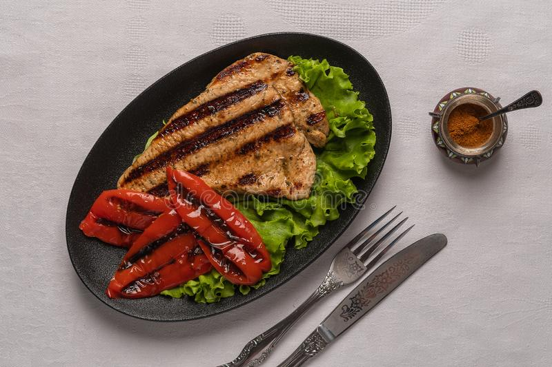 Grilled turkey breast steak with baked peppers and lettuce leaves in a oval black plate with knife and fork on a light. Homemade grilled turkey breast steak with stock photo