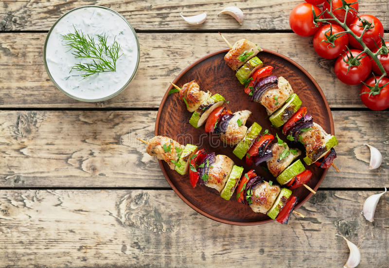 Grilled turkey or chicken meat shish kebab skewers with tzatziki. Sauce, chopped parsley, garlic and tomatoes on rustic wooden table background. Traditional royalty free stock photos