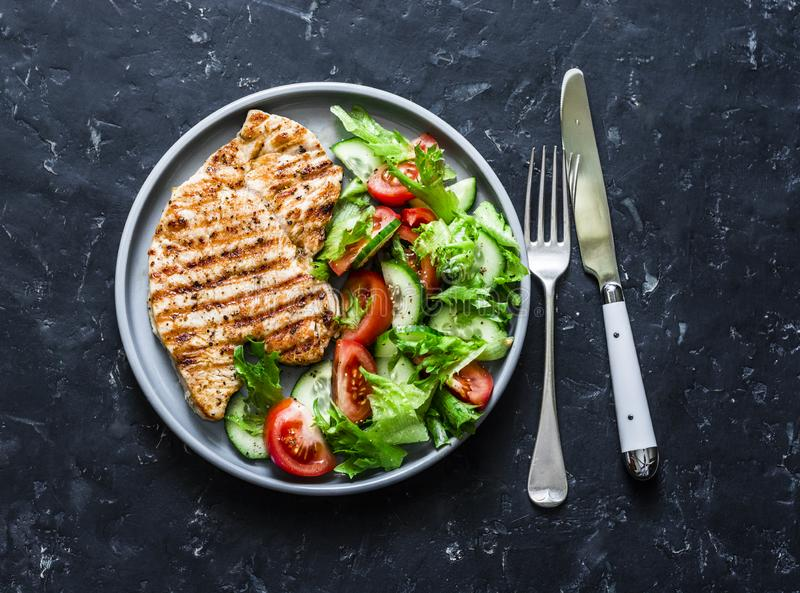 Grilled turkey chops and tomatoes, cucumbers, greens salad on a dark background, top. Healthy food diet concept. Grilled turkey chops and tomatoes, cucumbers royalty free stock images