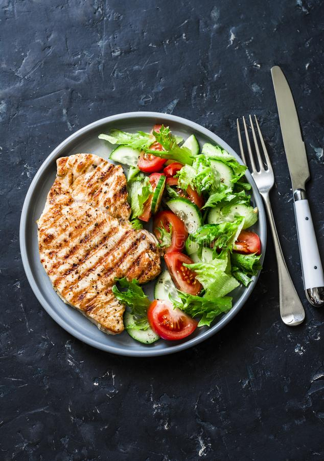 Grilled turkey chops and tomatoes, cucumbers, greens salad on a dark background, top. Healthy food diet concept stock image