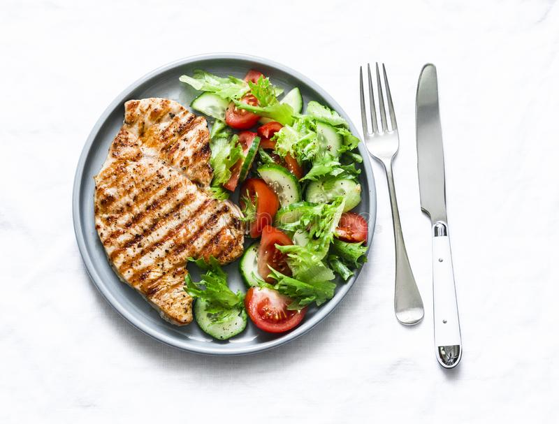 Grilled turkey chops and vegetables salad on a light background, top view. Healthy food diet concept. Grilled turkey chops and vegetables salad on a light stock photography