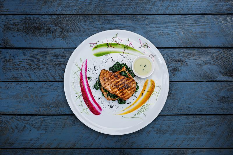 Grilled turkey fillet with greens. Grilled turkey fillet with greens, served on the white plate with wooden background. Top view royalty free stock photography