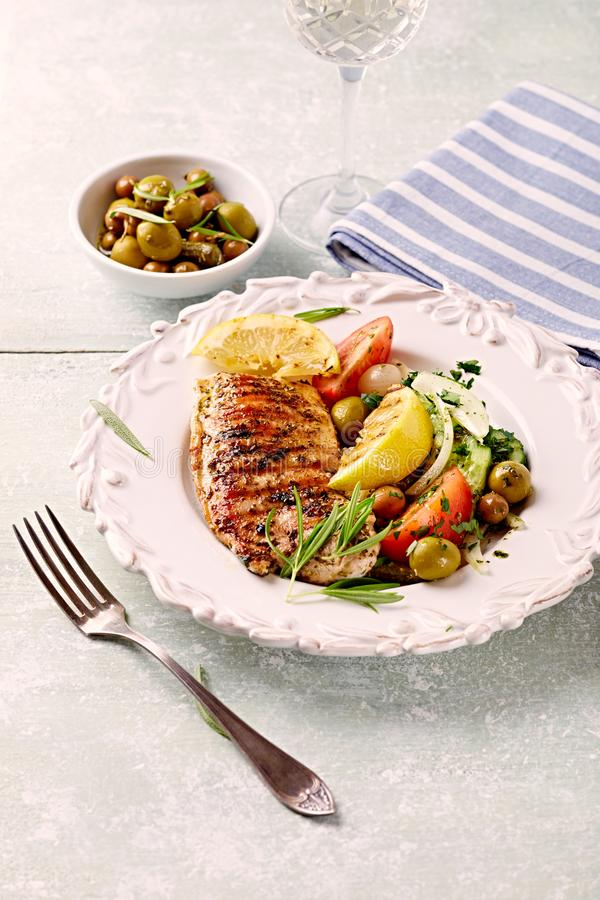 Grilled turkey fillet with grilled lemon and salad royalty free stock photo