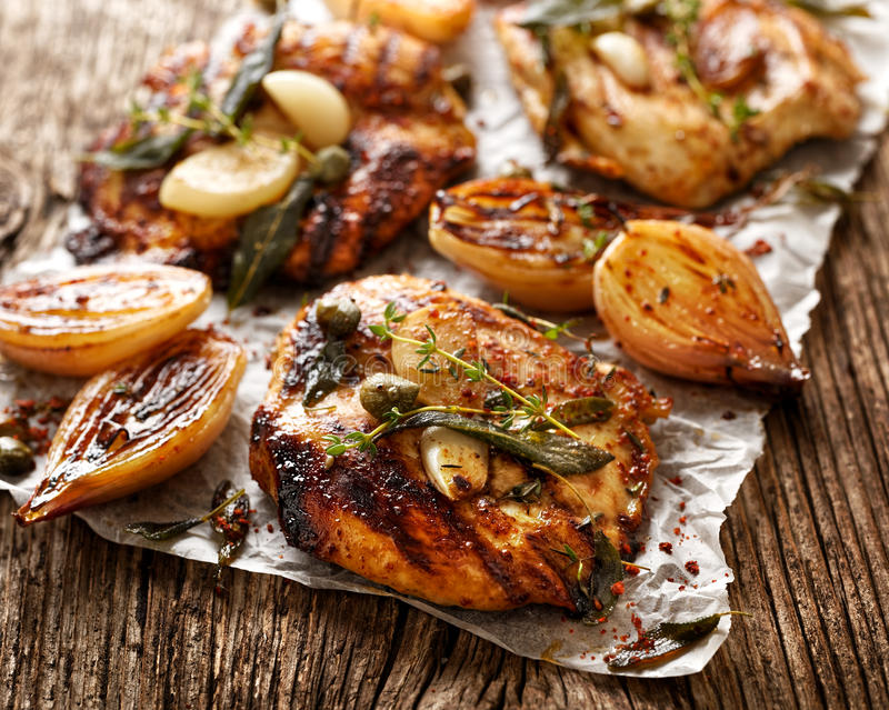 Grilled turkey fillet steak with addition herbs and shallot onions. On a wooden table stock photography