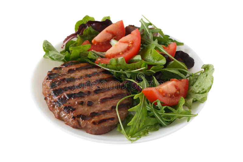 Grilled turkey hamburger with vegetable salad stock image