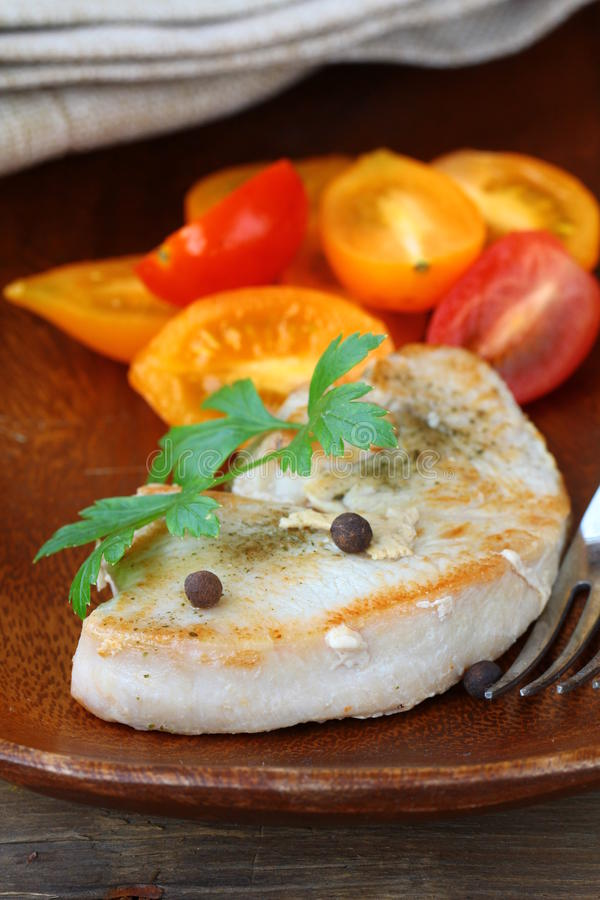 Grilled turkey steak. With a salad of tomatoes royalty free stock photos
