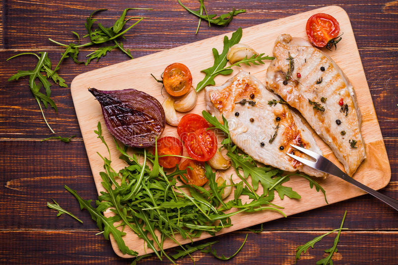 Grilled turkey steak on a cutting board. And a brown wooden background stock images
