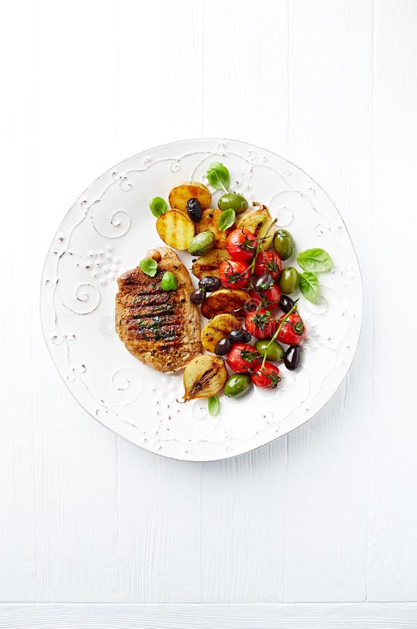 Grilled turkey steak with vegetables and fresh basil leaves on a plate royalty free stock photography